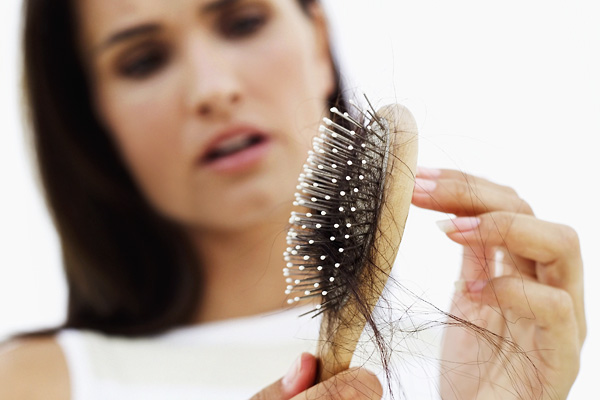 woman distraught at hair loss